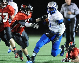 Hubbard #1 Darnell Tate runs the football before being hit by Canfield #57 Alex Heldreth during the 1st quarter of Friday nights game.