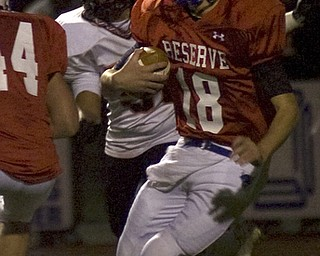 Kelli Cardinal/The Vindicator .Western Reserve quarterback Nick Allison carries the ball Friday night against Wellsville defenders on the Blue Devils field in Berlin Center.