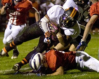 Kelli Cardinal/The Vindicator .Wellsville running back Brendon Carr holds onto the ball Friday night against Western Reserve defenders on the Blue Devils field in Berlin Center.