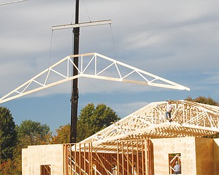Dale Murphy guides the positioning of trusses on Boardman Baptist Church, where he is working with Martin Eaton through Baptist Church Planters of Grafton, Ohio. The expansion of the church on Shields Road includes new sanctuary, offi ces and choir room. Construction began in June, and projected completion is September 2014.