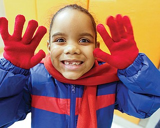 Diamonique Washington, a Harding Elementary School student, shows off the new coat, gloves and scarf she got from the Rotary Club of Youngstown. The club raised nearly $18,000 to buy coats and scarves for all the students at the Youngstown school. Youngstown State University's Rotaract Club raised money to buy the gloves.