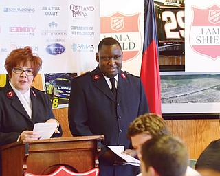 Salvation Army Majors Valerie and Elijah O. Kahn, Mahoning County area services coordinators, introduce the keynote speaker, Gary Meszaros, owner of Quaker Steak & Lube in Boardman, during Thursday's 2013 Red Kettle Campaign kickoff breakfast. The kettles and bell ringers will be at area shopping centers beginning Monday .