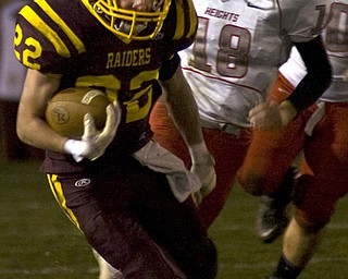 Kelli Cardinal/The Vindicator .South Range running back Billy Goodall carries the ball past Cuyahoga Heights defender Chandler Holesovsky during the first half Friday night at Memorial Field in North Lima.