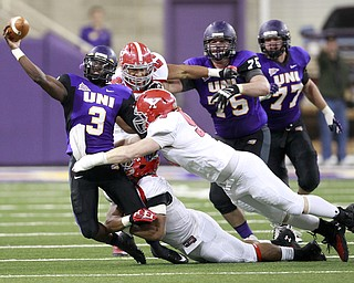 Northern Iowa quarterback Brion Carnes just gets a pass away before being tackled by Youngstown State defenders in the second half of the game at the UNI-Dome in Cedar Falls, Iowa, Saturday, Nov. 9, 2013.