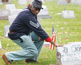 Steffon Jones, a local historian, places his hand on his father's headstone. George W. Jones Jr., known for his singing talent, served three years in the Air Force during the 1950s.