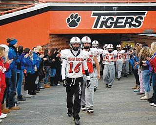 """Supported by a group of family and friends, the Sharon High football team walks out onto the field Sunday for their first practice since Friday's auto accident that claimed the lives of two teammates and left two more hospitalized. The tragedy came a day before the Tigers were to face Girard (Pa.) in Round 1 of the PIAA playoffs, which will be played tonight in Erie. Players will wear stickers with """"C.S."""" and """"E.G."""" on their helmets to honor teammates Corey Swartz and Evan Gill, who were killed."""