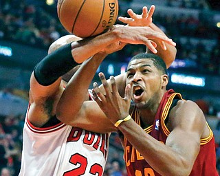 Bulls forward Taj Gibson (22) fouls Cavaliers forward Tristan Thompson during the first half of Monday's game in Chicago. The Cavs lost, 96-81.