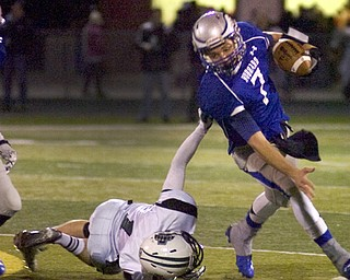 Kelli Cardinal/The Vindicator .Hubbard quarterback Brennan Wassil attempts to avoid the tackle Friday night by Aurora defender Kirk Janoch at Falcon Field in Austintown.