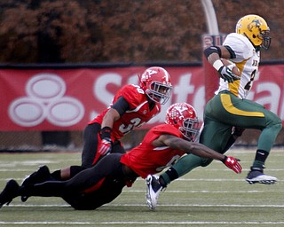 MADELYN P. HASTINGS | THE VINDICATOR..YSU's Tre' Moore (30) and Travis Williams (6) take down NDSU's John Crockett (23) during their game at Stambaugh Stadium on November 16, 2013. The Penguins lost to Bisons 17-35.... - -30-..