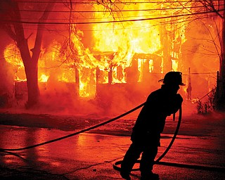 Youngstown firefighters attempt to put out a massive fire at a vacant house located off Market Street in Youngstown.