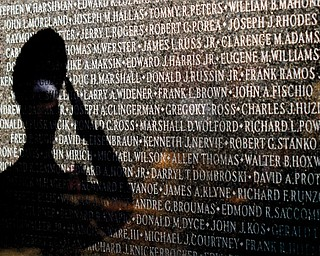 A shadow of a salute in memory of a loved one on the Vietnam War memorial in downtown Youngstown during the 22nd annual Laying of the Roses ceremony.