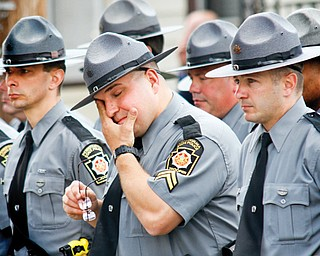 """A Pennsylvania State Police officer wipes away tears while standing with hundreds of police officers outside St. Vitus Church during a funeral service for Shenango Township Police Officer William """"Jerry"""" McCarthy, who was killed by Kylee Barletto in a car chase May 2, 2013."""