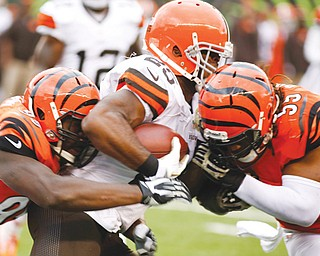 Browns RB Chris Ogbonnaya fumbles as he is hit by Bengals defenders Vontaze Burfict (55) and defensive end Wallace Gilberry (95) during the second quarter of Sunday's game in Cincinnati. Burfict recovered the ball and returned it for a touchdown. The Bengals scored three more times in the second quarter to set a team record and breezed to a 41-20 victory.