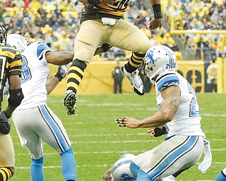 Steelers RB Le'Veon Bell leaps for more yardage as he tries to evade Lions defenders, including strong safety Glover Quin (27), during Sunday's game at Heinz Field in Pittsburgh. The Steelers, down 27-23 late in the fourth, scored two touchdowns in the final five minutes to vault over the Lions, 37-27.