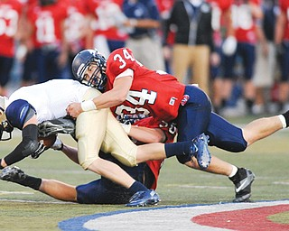 Fitch defenders Sam Ortz (34) and Ryan Sayers drag down Hoban's Jake Tersigni on a sweep play during a regular-season game at Falcon Stadium in Austintown. For the third time in 28 seasons, the Falcons are practicing for a Week 13 game. They take on Lakewood St. Edward on Friday in the Division I state quarterfinal in Akron.