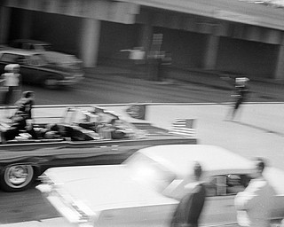 President Kennedy's limousine speeds along Elm Street toward the Stemmons Freeway overpass moments after he was shot at Dealey Plaza in Dallas, Tex., Nov. 22, 1963. Secret Service agent Clint Hill is seen on the back of the car as Jacqueline Kennedy tends to her fatally wounded husband.