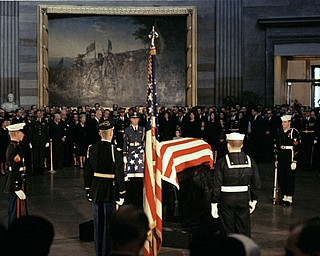 The flag-draped casket of President John F. Kennedy lies in state in the East Room of the White House in Washington, Nov. 23, 1963.