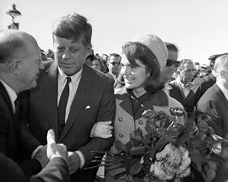 President John F. Kennedy and first lady Jacqueline Kennedy on their arrival at the Dallas Airport (Love Field) on Nov. 22, 1963. They are greeting unidentified people. (AP Photo/HWB)