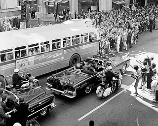 U.S. President John F. Kennedy and first lady Jacqueline Kennedy are riding in the backseat of an open limousine  on Main Street at Ervay Street as the presidential motorcade approaches Dealey Plaza in downtown Dallas, Texas, on November 22, 1963. Only moments later the ride ends in the president's assassination. Texas Gov. John Connally, who will be wounded in the ambush attack, and his wife Nellie are seated in the limousine's jump seat.