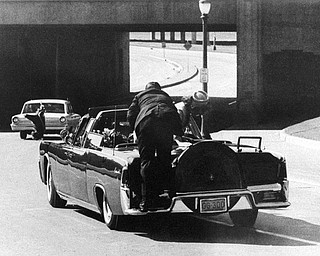 President John F. Kennedy slumps down in the back seat of the Presidential limousine as it speeds along Elm Street toward the Stemmons Freeway overpass after being fatally shot in Dallas on Nov. 22, 1963.  Mrs. Jacqueline Kennedy leans over the president as Secret Service agent Clinton Hill rides on the back of the car.  (AP Photo/Ike Altgens)