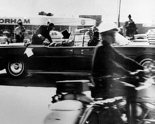 Secret Service agent Clint Hill climbs into the back seat of the limousine a moment after President John F. Kennedy and Governor John Connally of Texas were shot in Dallas, Nov. 22, 1963.  Black arrow points to Mrs. Connally ducking bullets, and white arrow points out the agent's foot, mistakenly thought to be the president's when the photo first ran.