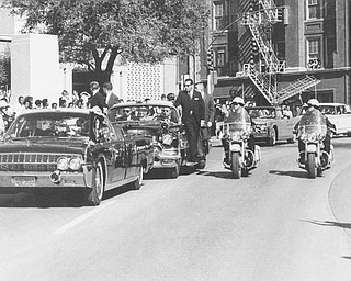 Seen through the limousine's windshield as it proceeds along Elm Street past the Texas School Book Depository, President John F. Kennedy appears to raise his hand toward his head within seconds of being fatally shot in Dallas, Nov 22, 1963. Mrs. Jacqueline Kennedy holds the President's forearm in an effort to aid him. Gov. John Connally of Texas, who was in the front seat, was also shot. (AP Photo/James W. (Ike) Altgens)