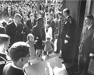 Mrs. Jacqueline Kennedy is seen entering St. Matthew's Roman Catholic Church with her children, Caroline and John, Jr., to attend the funeral mass for her husband John F. Kennedy in Washington, D.C., on Nov. 25, 1963. Behind them is Sen. Edward M. Kennedy of Massachusetts.