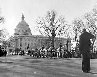 A horse-drawn caisson carrying the flag-draped casket of the late President John F. Kennedy moves out of the Capitol plaza en route to St. Matthew's Cathedral for funeral services, Nov. 25, 1963.