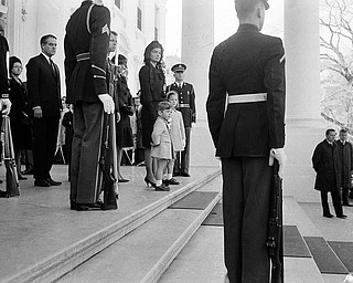 Jacqueline Kennedy and her two children, John Jr. and Caroline stand at the top steps of the Executive Mansion as the body of President John F. Kennedy is carried from the Executive Mansion to lie in state at the Capitol, Nov. 24, 1963.
