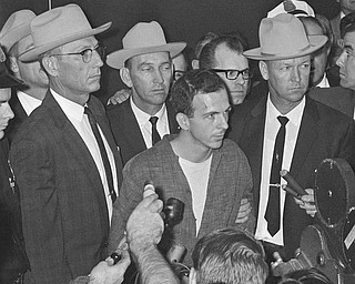 """Lee Harvey Oswald is shown early Nov. 23, 1963, as he stood before newsmen in a Dallas police station where he repeatedly denied that he had assassinated President Kennedy yesterday.  """"I did not kill President Kennedy,"""" he said. """"I did not kill anyone. I don't know what this is all about."""" He was brought before the newsmen just after formal charges of murder were filed against him."""