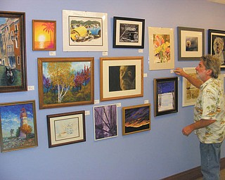 SPECIAL TO THE VINDICATOR:   More than 100 pieces of original art are for sale on the first floor of Trumbull Memorial Hospital, 1350 E. Market St., Warren, in the Nissen Gallery. Local artists will be the feature of the 2013 Trumbull Area Artists Holiday Show. Each piece is priced at $100 or less. Purchases can be made through Peg Krozier in the hospital's administration office or by calling 330-841-1900. The display will run through Jan. 2. Above is James Hardy of Warren, who assisted hanging the art for the show.