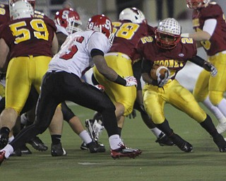 Cardinal Mooney's C.J. Amill (2) cuts through a hole in the Steubenville defense before being met by Steubenville's Jeremy Blue (25) during the second quarter of Friday nights Division four Semi-Finals matchup at Fawcett Stadium in Canton.  Dustin Livesay     The Vindicator  11/29/13  Fawcett Stadium, Canton.