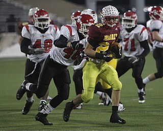 Cardinal Mooney's Mark Handel (22) runs through the Steubenville defense with Branden Jones (46) on his heels during the second half of Friday nights Division four Semi- Finals at Fawcett Stadium in Canton.  Handel rushed 14 times for 52 yards during the Cardinals 37-7 victory over Big Red.    Dustin Livesay     The Vindicator  11/29/30  Fawcett Stadium, Canton Ohio.