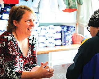 Melanie Rauschenbach, owner of Kid's Stuff in Struthers, talks with the son of a customer, Cody Straley, 14. The children's resale shop recently moved from State Street to Lowellville Road.