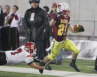 Cardinal Mooney's Mark Handel (22) eludes a tackle by Steubenville's Bryan Pierro (7) during the second quarter of their Division IV semifinal game at Fawcett Stadium in Canton.