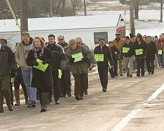 Local social-service agency leaders march on Monday from the St. Vincent de Paul Society soup kitchen on Front Street in downtown Youngstown to the Rescue Mission of Mahoning Valley on Martin Luther King Jr. Boulevard, also in Youngstown, symbolically tracing the footsteps of homeless people, who often make this trek in harsh winter weather.