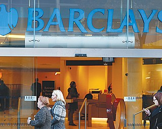 People walk past a branch of Barclays Bank in London on Wednesday. The European Commission has fined a group of major global banks, including Barclays, a total of $2.3 billion for colluding to profit from the interest-rates market. The banks are accused of manipulating for years European and Japanese benchmark interest rates that affect hundreds of billions of dollars in contracts globally, from mortgages to credit card bills.