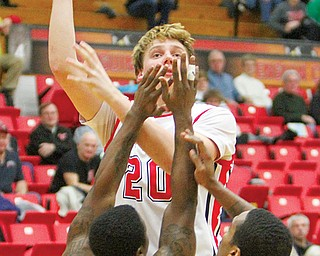 Youngstown State's Bobby Hain shoots over Robert Morris defenders Anthony Myers-Pate (5) and Mike McFadden (1) during their game Wednesday at Beeghly Center. The Penguins downed the Colonials, 84-76.
