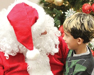 Zachary Krk, 3, of Struthers sits on Santa's lap while reviewing his Christmas wish list. Santa visited Mauthe Park in Struthers on Thursday as part of the city's annual Christmas in the Park event.