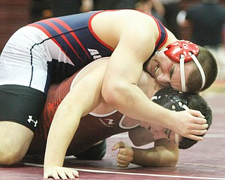 Fitch's Blake Hibbs, top, tries to pin Boardman's AJ Yaist during their match in the 220-pound weight class of a tri-meet at Boardman High School on Thursday. Hibbs succeeded in pinning Yaist, and the Falcons took down the Spartans, 54-10, as well as the Howland Tigers, 53-15. Howland topped Boardman, 40-30.