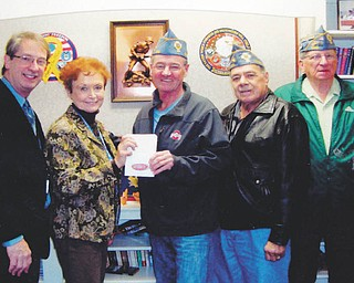 Catholic War Veterans Post 1292 of Youngstown sponsored a reverse raffle and basket auction recently to benefit veterans and their families. From left are Mark Bell, director of the Veterans Affairs Clinic on Belmont Avenue in Youngstown; Lori Stone, a clinic volunteer, who accepted the $1,200 donation from Gary Barnes, the post commander; Al Bisker, post trustee; and John Fromel, post first vice officer. SPECIAL TO THE VINDICATOR