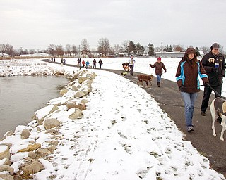 Owners and their dogs start on the trail Sunday during the MetroMutts Jingle Hike at the Mill Creek MetroParks Farm in Canfield.