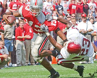 Ohio State tailback Maurice Clarett (13) fends off a tackle attempt by Indiana free safety A.C. Carter (23) during a game at Ohio Stadium. Clarett, a former Warren Harding High School standout, helped the Buckeyes win the national championship that season. It ended up being his only season at Ohio State.