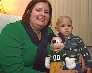 """Sixteen-month-old Dalton Bodnar relaxes with his mother, Dana Bodnar, and his Mickey Mouse toy. Dalton, who has been declared cancer-free after three rounds of chemotherapy, will be the guest of honor with VIP seats at tonight's opening performance of """"Disney on Ice"""" at the Covelli Centre."""