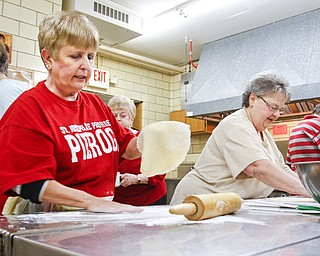 Tess Szenborn, above left, and Paulette Jamrozik roll out dough to make kolachi during a Wednesday baking session at St. Joseph the Provider Church of Christ, The Good Shepherd Parish in Campbell. They're preparing for a Cookie Walk on Saturday sponsored by St. Joseph Cultural Society. Below, dough is spread with a layer of nuts during the kolachi-making project. The Cookie Walk will feature homemade cookies including clothespin and pizzelles along with kolachi.