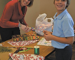 SPECIAL TO THE VINDICATOR:  Students at Holy Family School in Poland recently enjoyed shopping at Santa's Workshop. Several small good quality gifts were available for purchase. Lisa Daprile, left, parent volunteer, wrapped the gifts that third-grader T.J. Richey bought for his family at the workshop.