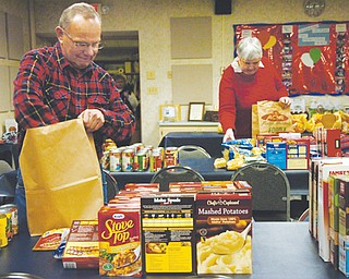 Dave Sylak, a member of St. Mary Church, and Carol Seifert, a member of Mineral Ridge Church of Christ, pack Christmas grocery bags Monday for distribution by Mineral Ridge Community Parish Association on Tuesday. The association helps those in need in Mineral Ridge and those who are members of association churches.