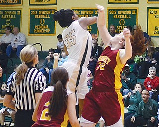 Ursuline's Tanaya Beacham swats the ball away from Cardina Mooney's Maggie Monahan at the start of Wednesday's game at Ursuline High School. Beacham scored 18 points for the Irish, who downed the Cardinals, 47-39.