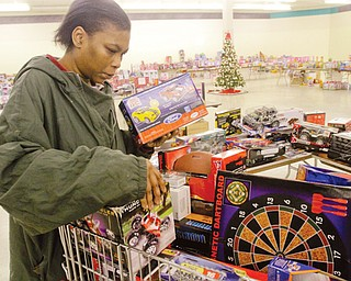 Nikesha Curry of Youngstown looks for Christmas gifts for her children in the toy section at the Salvation Army's distribution center in the Austintown Plaza on Mahoning Avenue. Families who have not registered for a shopping day at the center can still sign up from 1 to 3 p.m. Friday .