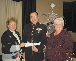 SPECIAL TO THE VINDICATOR Warren Republican Women's Club raised $2,200 during its annual Toys for Tots Auction early in December at McMenamy's in Warren. In attendance for the check presentation were, from left, Kelly Pope, the club's second vice president and chairman of the auction; U.S. Marine Sgt. Modesto Montano; and Cary Ann Koren, club president.